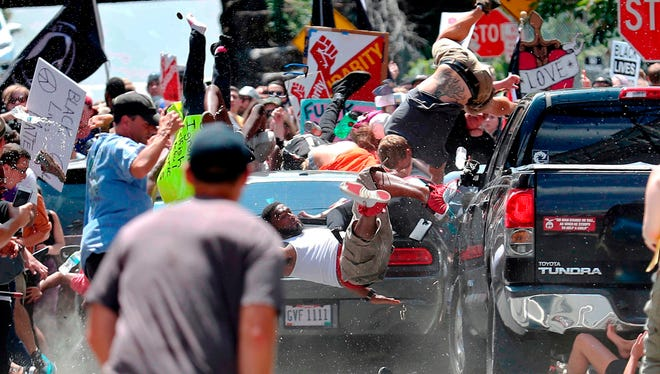 In this Aug. 12, 2017, photo by Ryan Kelly of The Daily Progress, people fly into the air as a car drives into a group of protesters demonstrating against a white nationalist rally in Charlottesville, Va.