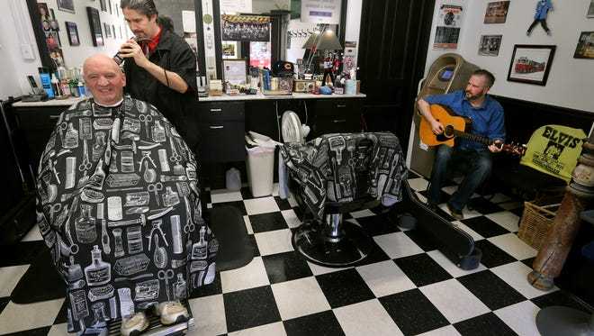 Timm Cash (L) keeps a guitar in O'Brien's  Barbershop on Main St. in Victor,  owned by his friend and music pupil Bill O'Brien.  Customers like Ron Coyle can enjoy the music when Cash  comes stops by to play.