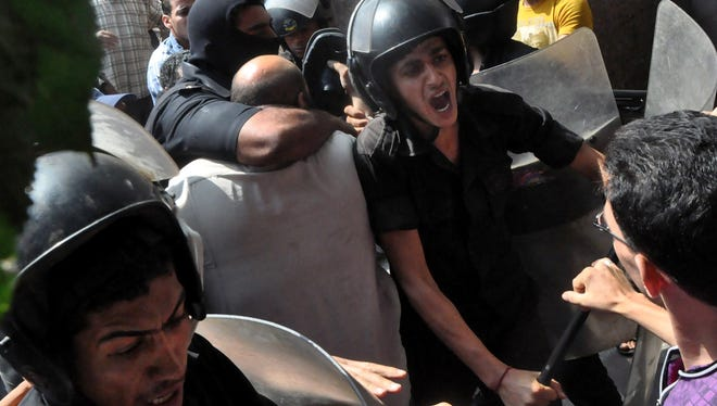 Egyptians security forces escort an Islamist supporter of the Muslim Brotherhood out of the al-Fatah mosque and through angry crowds near Ramses Square in downtown Cairo, Saturday.
