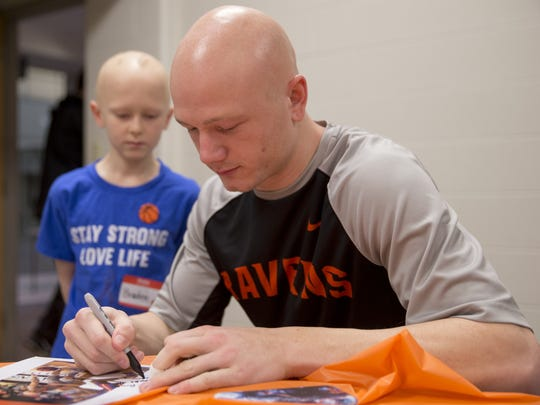 Trevor Lucas signs an autograph for fellow person with alopecia Braden Burkholder, 9, Brownsburg, during an event for people with alopecia before the night's game against Manchester at Anderson University, Wednesday, Feb. 7, 2018. Alopecia is a medical condition that causes hair loss.