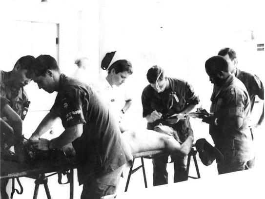 David Carden, second from left, works on a patient