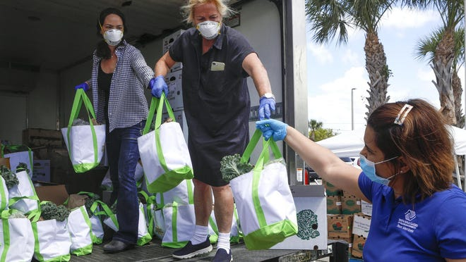 Margaret Duriez, left, and Lily Busch Holt Dillon hand bags of food to Soniann Balasquide on Friday that will be given to families of children who are members of the Max M. Fisher Boys & Girls Club in Riviera Beach.