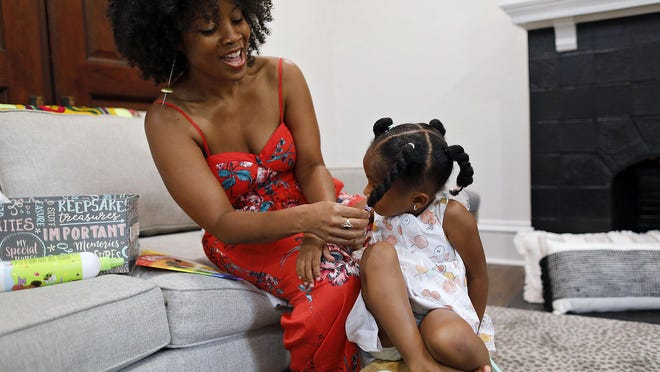 """Carlotta Penn, creator of """"The Turtle with an Afro"""" book and a more recent animated version, styles the hair of her 3-year-old daughter, Jember, at their home."""