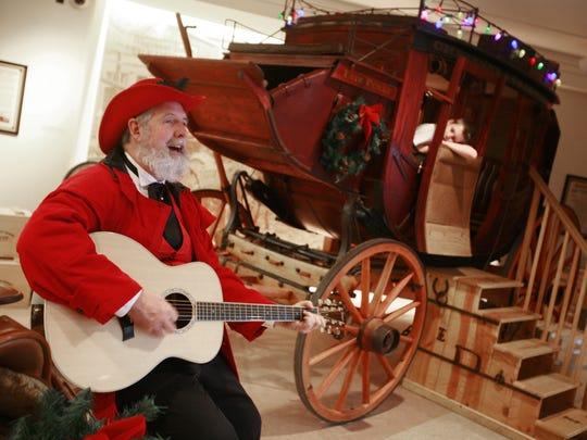 Cowboy Santa Mike Flowers sings western holiday songs during the Eiteljorg Winter Market in 2008.