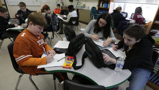 Jacob Cornell, Talia Sheehan and Maddie Asen work on a project involving messenger RNA and amino acids Wednesday, Jan. 4, 2017, during science class in the ALPS program at Perry Tipler Middle School.