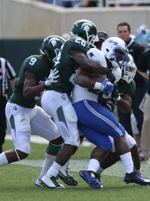 Michigan State's RJ Williamson tackles Air Force's DeAnthony Arnett during second half action on Saturday, September 19, 2015 at Spartan Stadium in East Lansing Michigan.