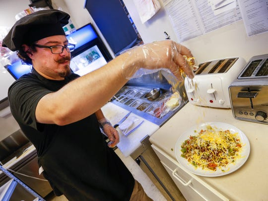 Omer Onder, owner of Springfield Diner, drizzles cheese over the Fiesta Skillet which includes two eggs, sautéed onion, peppers and tomatoes, a beef patty, hashbrowns and chili.