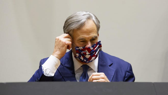 Gov. Greg Abbott takes off his mask before speaking at a press conference with local officials concerning protest violence, on Tuesday at Dallas City Hall.