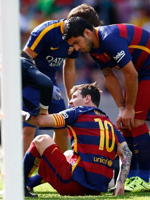 FC Barcelona's Lionel Messi, from Argentina, sits on the pitch after being injured,  during a Spanish La Liga soccer match against Las Palmas at the Camp Nou stadium in Barcelona, Spain, Saturday, Sept. 26, 2015. (AP Photo/Manu Fernandez)