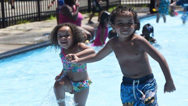 Sean Johnson, 4, right, and Samantha Johnson, 2, left,  of the City of Poughkeepsie splash through the wading pool at Pulaski Pool on Washington Street in the City of Poughkeepsie.