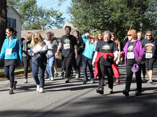 Walkers and runners start the 5K walk during the Annual