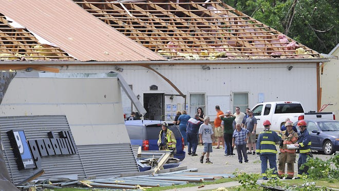 Rescue workers and others congregate at the partially collapsed Goodwill store in Portland after severe storms Monday. The Ionia County Central Dispatch reported that three people were trapped in the store on Grand River. They were rescued without injuries.