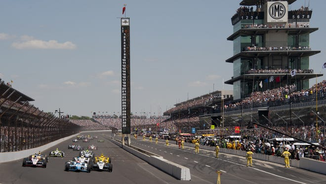 James Hinchcliffe takes the lead from pole winner Ed Carpenter at the start of the 98th running of the Indianapolis 500 at the Indianapolis Motor Speedway. Sunday, May 25, 2014.