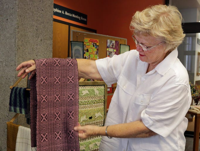 Doris DeYoung of the Shuttlecraft Guild holds a completed weaved shawl during a display Saturday August 9, 2014 at Mead Public Library.