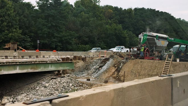 Workers move equipment, Saturday, August 29, 2015, near the northbound Interstate 65 bridge near Lafayette. Repairs to the bridge over Wildcat Creek are underway and the highway is on schedule to reopen mid-September, officials said