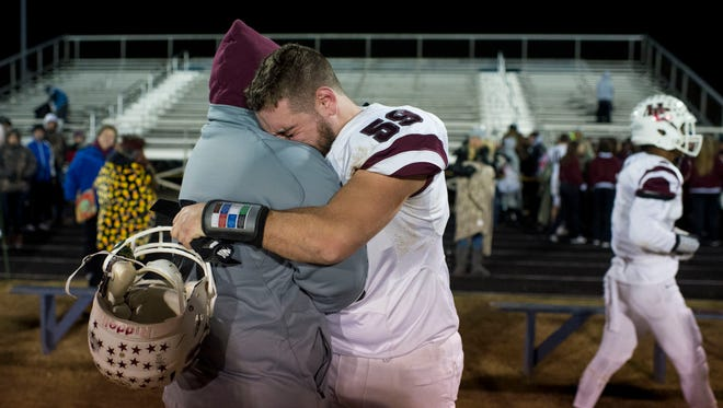 Henderson County's Caleb Sellars (59) gets a hug after their 31-16 loss to Central Hardin at Central Hardin High School in Cecilia, Ky., on Friday, Nov. 10, 2017.