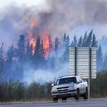 "Flames flare up from hotspots from a wildfire along a highway to Fort McMurray, Alberta, Canada, Sunday, May 8, 2016. Officials said Sunday they reached a turning point in fighting an enormous wildfire, hoping to get a ""death grip'"" on the blaze that devastated Canada's oil sands town of Fort McMurray amid cooler temperatures and light rain. (Ryan Remiorz/The Canadian Press via AP) MANDATORY CREDIT"