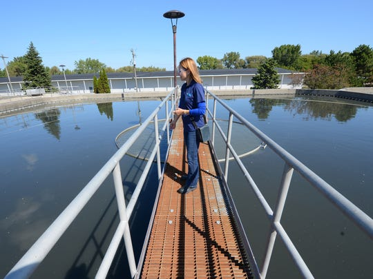Tricia Garrison of NEW Water stands on a catwalk over a 30 foot deep skimmer tank at the wastewater treatment plant on Quincy Street in Green Bay September 17, 2014.  Jim Matthews/Press-Gazette Media