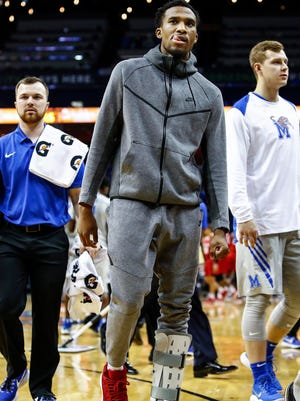 Memphis guard Jeremiah Martin (middle) walks back to the bench in an ankle boot during a break in action against Houston at the FedExForum in Memphis Tenn., Thursday, February 22, 2018.