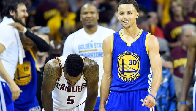 Golden State Warriors guard Stephen Curry (30) reacts next to Cleveland Cavaliers guard J.R. Smith (5) in the closing seconds of game six of the NBA Finals at Quicken Loans Arena.