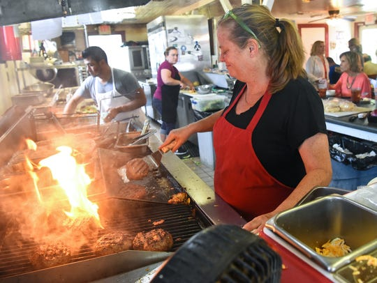 Owner Heidi Truell flips burgers on the grill during