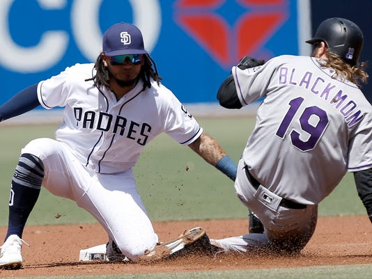 San Diego Padres shortstop Freddy Galvis tags out Colorado Rockies' Charlie Blackmon on an attempted steal on the pitcher during the first inning of a baseball game in San Diego, Thursday, April 5, 2018. (AP Photo/Alex Gallardo)