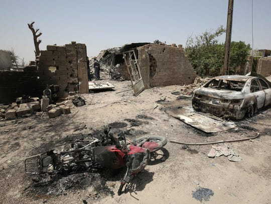 A June 30, 2016, photo shows damaged vehicles in Fallujah,