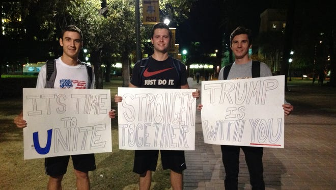 (From left) Jacob Mumme, Chaz Simmons and Matthew Wichman show support for President-elect Donald Trump in Tempe on Nov 9.