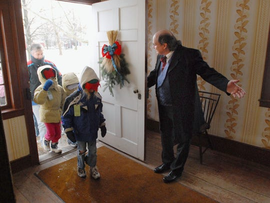 John MacKay, right, played by Gian Cervono of Rochester, welcomes guests into his homestead for a Scottish feast at the Genesee Country Village and Museum's Yuletide in the Country: A Very Merry Yuletide holiday festival in Mumford.