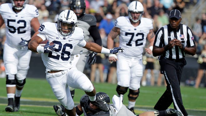 Penn State running back Saquon Barkley (26) runs out of the tackle of Purdue linebacker Markus Bailey (21) during the first half of an NCAA college football game in West Lafayette, Ind., Saturday, Oct. 29, 2016.