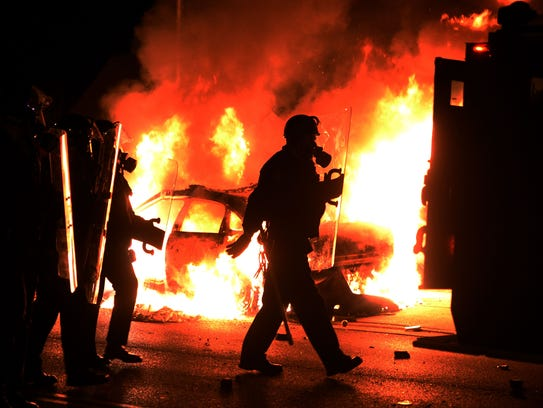 Police in riot gear pass one of their burning cars