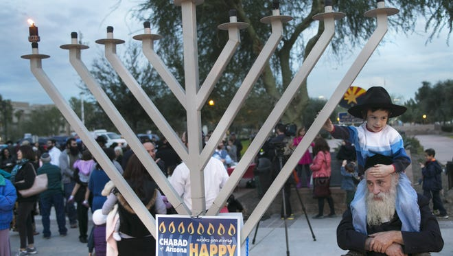 Moshe David Margolin, 6, sits on the shoulders of his father, Chaim Margolin of Phoenix, as they stand by the menorah after Gov. Jan Brewer lit the menorah on the first night of Hanukkah at the Arizona State Capitol in Phoenix on Tuesday, Dec.16, 2014.