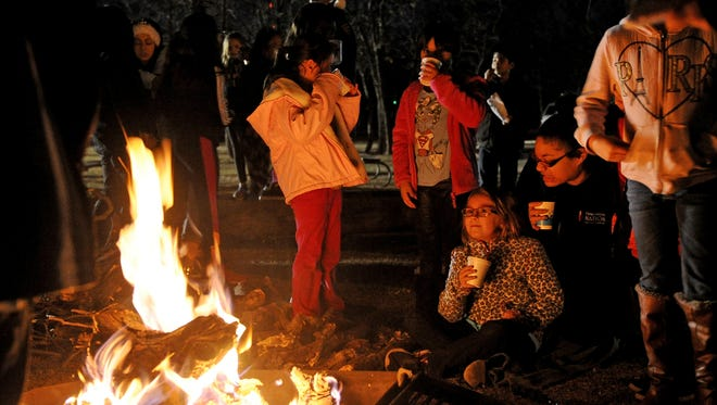 Campers drink hot chocolate and stay warm by the fire Thursday, Dec. 7, 2017, at Camp Fire.