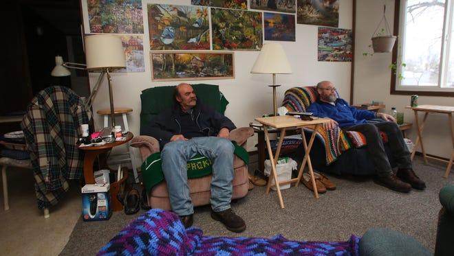 Lester Gruhlke, left, and Tony Narlock share Narlock's Wausau apartment, where Gruhlke sleeps on the recliner.