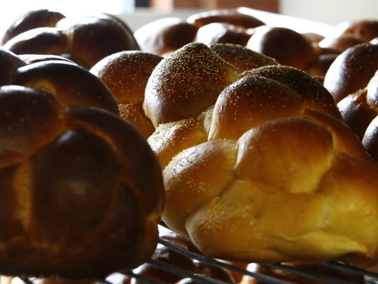 Plain challah sits on cooling racks in the production