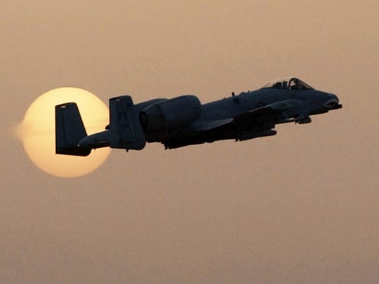 An A-10 fighter takes off past the setting sun during