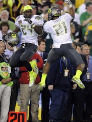 Oregon's Kenjon Barner (24) and LaMichael James celebrate a two-point conversion during the first half of the BCS National Championship game against Auburn on Jan. 10, 2011.