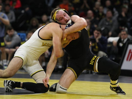 Iowa's Alex Marinelli wrestles Michigan's Logan Massa at 165 pounds during the Hawkeyes regular-season meet against Michigan at Carver-Hawkeye Arena in Iowa City on Saturday, Jan. 27, 2018. Marinelli went on to win the match 3-2 whereas the Hawkeyes would fall to the Wolverines in team points 17-19.