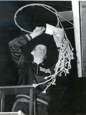 Bobby Plump of Milan High School cut down the net after winning the 1954 state boys basketball championship.