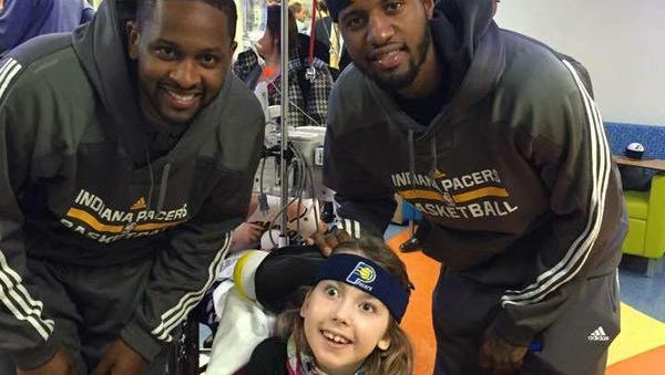 Indiana Pacers C.J. Miles (left) and Paul George hanging with Daisy.