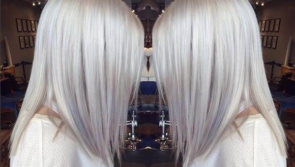 A client models an icy blonde hair color at Poppy Salon.