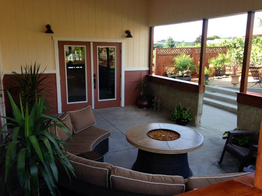 The cozy covered patio at the tasting room has a seating area and a fire pit.