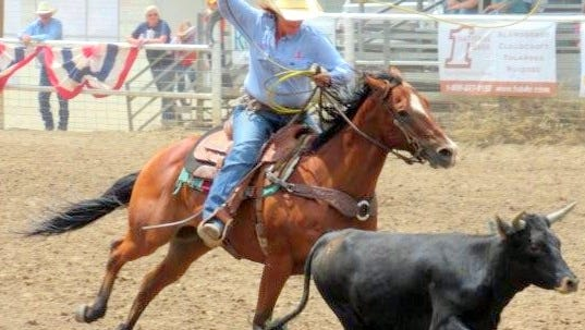 Almost there, a contestant in the Women's Rodeo during the annual Smokey Bear Stampede in Capitan zeros in on a calf.
