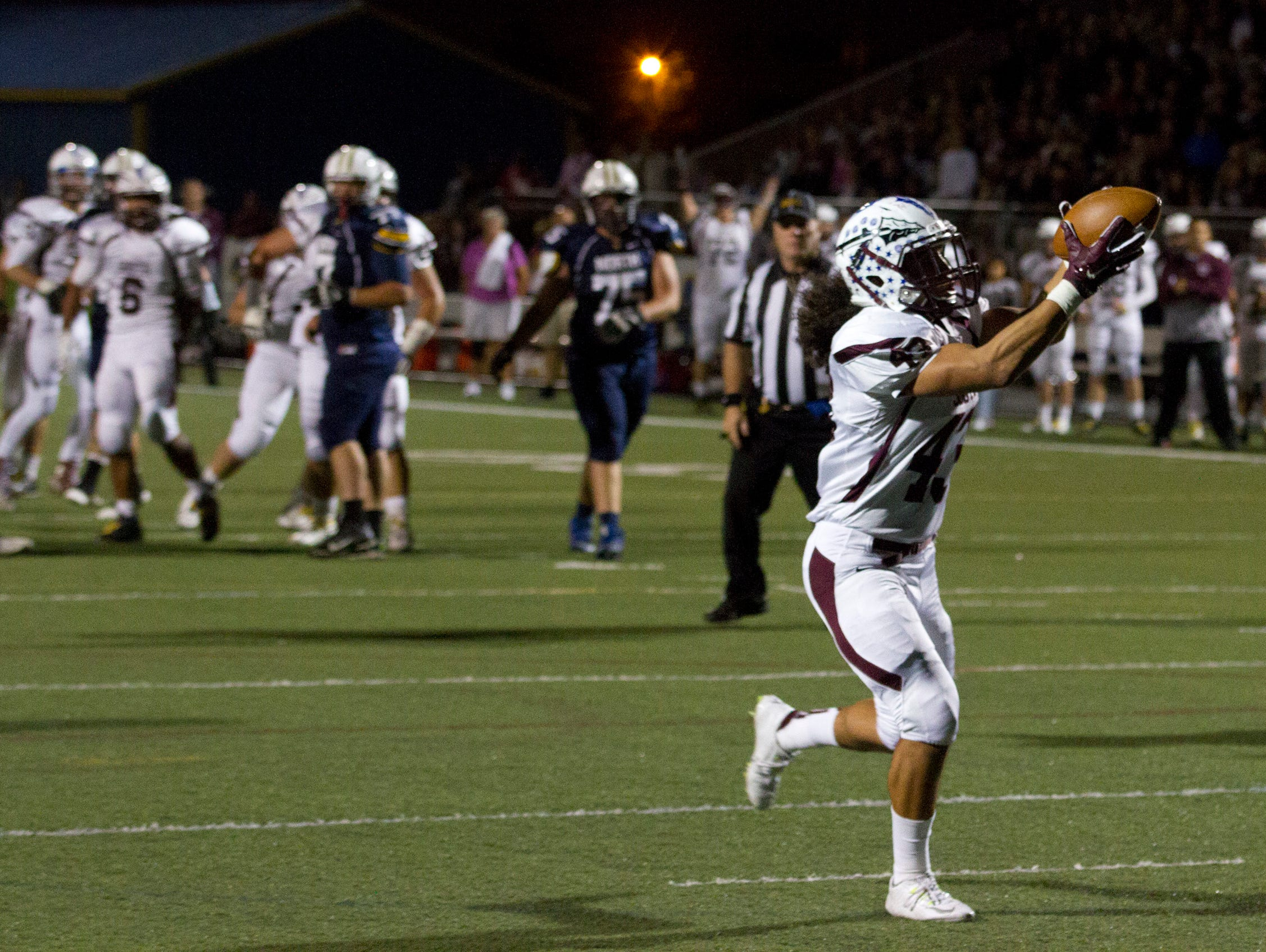 Toms River South's Tyler Sosa catches a pass over the middle and takes it in for his teams first touchdown. Toms River South vs Toms River North Football in Toms River NJ on September 25, 2015.