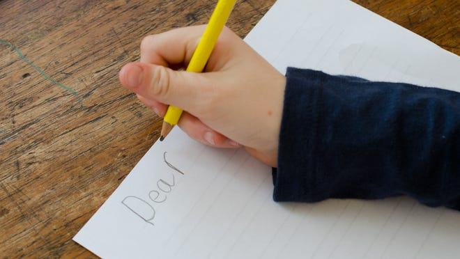 Child writing a letter starting with Dear