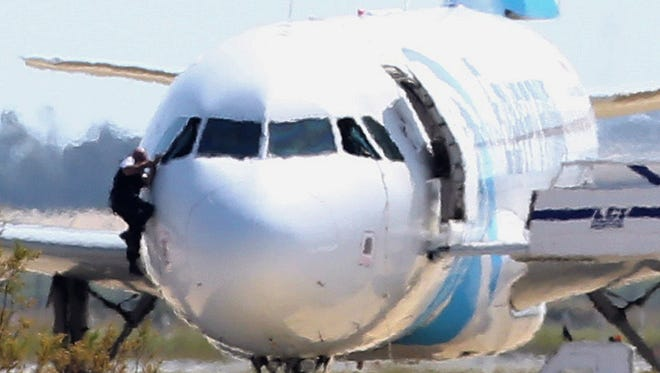 A man leaves the hijacked Egyptair aircraft  from the pilot's window after landing at Larnaca airport.