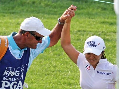 Sei Young Kim high fives her caddie Paul Fusco after sinking a flop shot for eagle on the par 5 15th hole during the second round of the KPMG Women's PGA Championship at Westchester Country Club in Rye June 11, 2015. Kim finished the day in first place at eight under par.(Photo: Seth Harrison/The Journal News)
