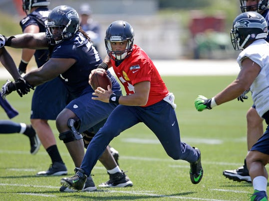 Seattle Seahawks quarterback Russell Wilson scrambles at an NFL organized team activity football practice Monday, June 2, 2014, in Renton, Wash. (AP Photo/Elaine Thompson)