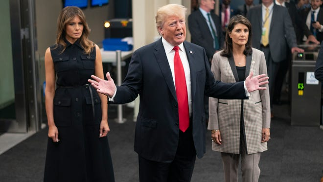 First lady Melania Trump listens as President Donald Trump addresses the media as they arrive with Nikki Haley, the U.S. ambassador to the United Nations, during the 73rd session of the United Nations General Assembly, in New York on Sept. 25, 2018. The first lady wore a sleeveless, belted black midi-dress by Christian Dior.
