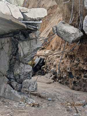 Debris dangles from the collapsed Tex Wash bridge  along Interstate 10 east of Indio in July 2015.